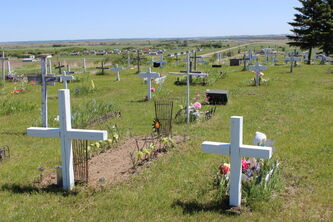 A view of the Anglican cemetery in Sioux Valley Dakota Nation, where many of the grave markers are white, wooden crosses.