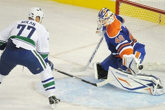 Vancouver Canucks' Owen Nolan, left, scores, on the Edmonton Oilers' goalie Devan Dubnyk during first period NHL pre-season hockey action in Edmonton on Thursday, September 22, 2011. THE CANADIAN PRESS/John Ulan