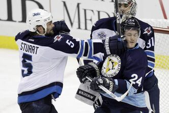 Jets defenceman Mark Stuart lets out a little frustration against Penguins forward Matt Cooke as goalie Ondrej Pavalec looks on during Saturday's messy loss.