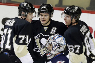 Pittsburgh Penguins left wing Chris Kunitz (14) celebrates his first-period goal with Evgeni Malkin (71) and Sidney Crosby (87) as Winnipeg Jets goalie Al Montoya (35) waits during an NHL hockey game in Pittsburgh, Thursday.