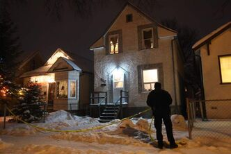 Winnipeg Police Service members string up tape at 907 Lipton Street Friday night after a woman was stabbed.