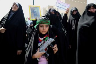An Iraqi girl living in Iran holds a toy gun with a headband which bears the name of Shiite Saint Hussein while joining a demonstration against Sunni militants of the al-Qaida-inspired Islamic State of Iraq and the Levant, or ISIL, and to support the Grand Ayatollah Ali al-Sistani, Iraq's top Shiite cleric, in Tehran, Iran, Friday, June 20, 2014.
