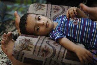 Two and a half-year-old Muhammad Al Masri rests on his mother's legs in a classroom at a United Nations school where hundreds of families have sought refuge after fleeing their homes following heavy Israeli forces' strikes, in Jebaliya refugee camp, Gaza Strip, Friday, July 25, 2014.