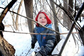 Five-year-old Owen Edmonds plays in a pretend cage made of sticks in the woods at Assiniboine Park Saturday. The structures were made by children and child-care workers in the early childhood education program as part of an initiative to get kids playing outside and creating things with nature.
