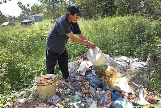 Geordie Rae from St.Theresa Point First Nation dumps a slop pail full of sewage in a dump outside his home.