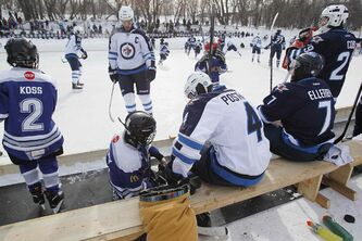 Winnipeg Jet Paul Postma (4) warms his gloves with a Portage Atom A player as hundreds of fans came out to support the Winnipeg Jets at an open outside practice at The Forks in Winnipeg Sunday.