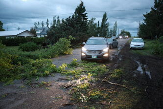 Vehicles try to navigate a street littered with debris in the community of Pipestone after a severe storm hit the community Saturday evening.