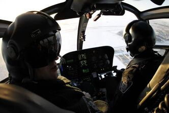 Const. Nick Paulet and pilot Renee Brindeau fly Air 1, the Winnipeg Police Service helicopter, above the city.