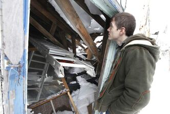 David Reid surveys the damage to his garage after its roof caved in early Sunday.