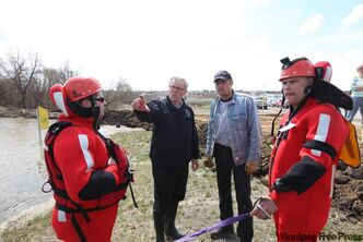 Manitoba Premier Greg Selinger and Brandon East MLA Drew Caldwell chat with Brandon Fire and Emergency Services members Trevor Falk and Sheldon Reynolds as they tour flooded areas along the Assiniboine River in Brandon along 18th Street on Sunday afternoon.