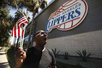 "DeWayne Williams, 48, from Los Angeles chant, ""freedom and justice for all -- no racism -- we don't need it,"" as he waves American flags marching in front of the Clippers headquarters in Playa Vista, CA, Monday."