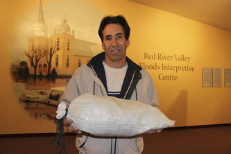 Jacques Courcelles holds a miniature sandbag, used to teach children about flood fighting.