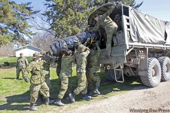 Soldiers from the Lord Strathcona's Horse Sqn. based out of Edmonton load an aqua dam into a truck close to the Hoop and Holler bend of the Assiniboine River.