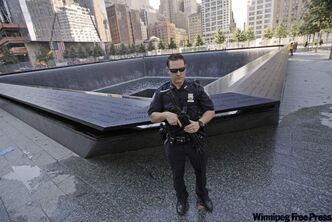 A heavily armed Port Authority police officer stands guard next to the North Pool at the World Trade Center memorial site on Friday.