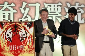 Taiwanese director Ang Lee, left, and lead actor from India Suraj Sharma accept gifts a during press conference announcing their new film