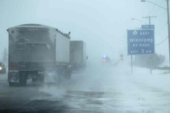 Motorists make their way into Winnipeg just west of the city in blowing snow Wednesday afternoon.
