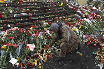 A man lights a candle at a memorial for the people killed in clashes with police at Independence Square in Kiev, Ukraine, Monday, Feb. 24, 2014.