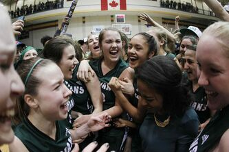 Members of the Vincent Massey Trojans celebrate a win over the Sisler Spartans to claim the AAAA provincial basketball championship at the University of Manitoba's Investors Group Athletic Centre Monday.