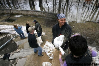 Mike Saria (centre) works sandbagging a house at 436 Assiniboine Avenue.