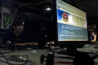 "Computer users sit near a display with a message from the Chinese police on the proper use of the internet at an internet cafe in Beijing, China, Monday, Aug. 19, 2013. China's newest opinion leaders - ranging from pop stars to scholars, journalists to business tycoons - exert their influence via microblogs known as ""Big Vs'' because the accounts are ''verified'' and popular. Authorities are now tightening the screws on these latest additions to the country's already constricted information stream. (AP Photo/Ng Han Guan)"
