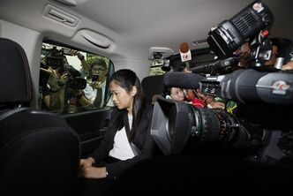 "Former fung shui practitioner Tony Chan Chun-chuen's daughter Polly Lon Pui-chun sits in a van after her father had been convicted and fined at the High Court in Hong Kong, Friday, July 5, 2013. The former lover of quirky billionaire Nina Wang has been sentenced to 12 years in prison after a Hong Kong court found him guilty of forging her will to claim her multibillion-dollar estate. A High Court judge on Friday called Peter Chan, formerly known as Tony Chan, ""shameless"" and ""wicked"" for taking advantage of Wang's trust in him. Chan is a former feng shui master who changed his name from Tony after converting recently to Christianity. (AP Photo/Kin Cheung)"