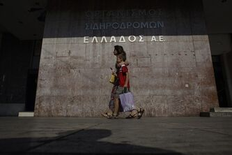 A woman and a boy walk in front of the closed central train station during a 24-hour strike in Athens, Tuesday, July 16, 2013. Greece's international creditors demanded job cuts before approving new bailout loan installments worth 6.8 billion euros ($8.9 billion) to be paid out between July and October. Parliament is to vote this week in the first major political test for Conservative Prime Minister Antonis Samaras since a left-wing party abandoned his coalition government last month.(AP Photo/Kostas Tsironis)
