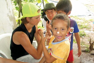 Evan Pfrimmer (left), of La Salle, communicates with some of the children he met during his recent mission to a village in El Salvador.