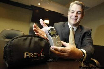 Christopher Moreau demonstrates new technology that measures cholesterol levels in a person's skin to assess the risk of heart disease.