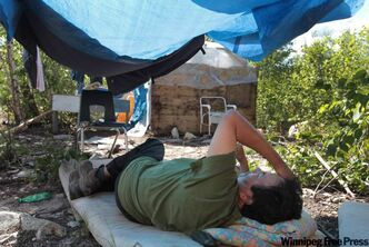 Bernard Flett lies under a tarp to get out of the hot sun. After living without running water, he waits as crews renovate his St. Theresa Point home and install plumbing.
