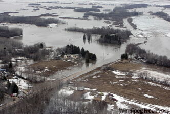 Breezy Point Road is left submerged Sunday after several shifts in the ice jam north of Selkirk forced river water to inundate dozens of homes in the RMs of St. Andrews and St. Clements.