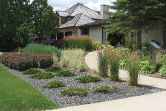Rectilinear beds of juniper and sedum greet visitors while curving swaths of ornamental grasses escort them to the front door