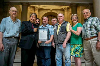 MLAs Ted Marcelino (Tyndall Park) and Melanie Wight (Burrows) presented members of Men in the Kitchen! with a copy of a Private Members Statement Marcelino delivered in the Legislative Assembly about the program on July 10. Pictured, from left to right: Wes Thomson, Marcelino, John Paton, Harvey Sumka, Harold Kuchenski, Tom Hutchinson, Wight, and Steve Mateush.