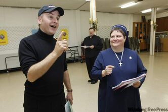 Award-winning composer Danny Schur gives instructions to Sister Janet Kozak as Father Mark Gnutel watches.