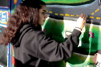 Sophia Rivera puts the finishing touches on the new mural at Elmwood High School.