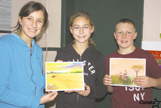 Domain Grade 7 students, from left to right: Carleigh Enns, Gabrielle Pereira and Jarret Magarrell holding up samples of their art.