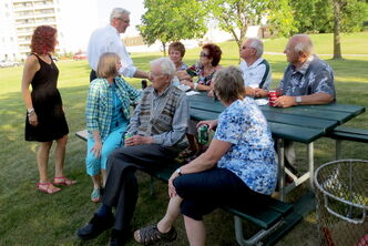 Kirkfield Park MLA Sharon Blady (far left) and Premier Greg Selinger (back row centre, standing) chat with constituents at the community barbecue held at Grant's Old Mill in August.