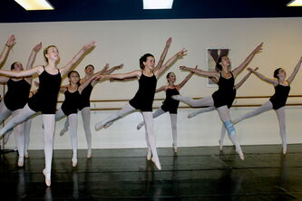 Ballet students leap into the air during a summer class at The Dance Centre