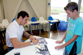 St. Louis Blues winger Alexander Steen signs a photo for a young fan at the grand opening of Great Big Adventure on Lorimer Blvd. on Friday.