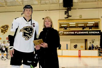 University of Manitoba Bisons men's hockey captain Dane Crowley receives the first ever Wayne Fleming Legacy Scholarship before Friday night's game against the University of Alberta Golden Bears. Also prior to the game, the arena within the Max Bell Centre on campus was renamed as the Wayne Fleming Arena.