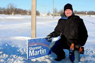 Progressive Conservative candidate Shannon Martin places campaign signs in the RM of Headingley on Dec. 31.