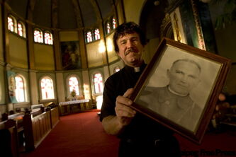 Father Taras Kowch with a portrait of his heroic grandfather, Father Emilian Kowcz.