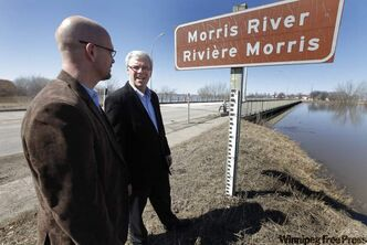 Manitoba Premier Greg Selinger (right) speaks with Gavin van der Linde, the mayor of Morris, the Morris River and highway 75 in Morris, about 50-km south of Winnipeg, Monday, April 11, 2010. The premier announced that highway 75 may be closed tomorrow due to the rising river. THE CANADIAN PRESS/John Woods