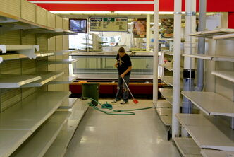 An employee helps clean the former Food Fare location at Arlington and Polson last week. Area businessman Todd Harris says he plans to reopen the grocery store, under his Harris Meats & Groceries banner, in September.