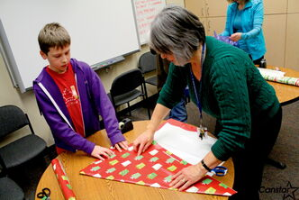 Grade 6 George Waters Middle School student Owen wraps a gift for a family member with the help of teacher Cheryl Latozke.