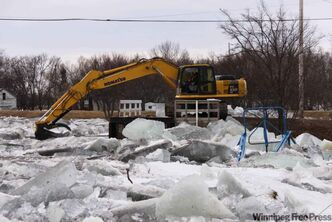 Workers attempt to clear an ice jam on the Icelandic River in Riverton Tuesday morning.