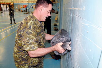Chief warrant officer Colin Stewart sweats through the 20-kilogram sandbag lift.