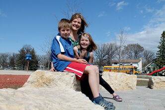Angela Janzen Roth and her children Bryn and Eric sit on one of 11 Tyndall stones circling the outdoor classroom.