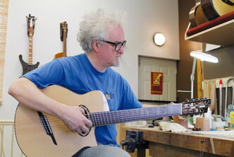 Allan Beardsell, in his new shop, tunes a freshly-strung, seven-string, fan-fretted multi-scale guitar he built.