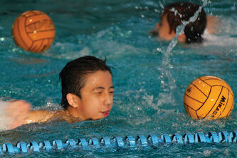 Timothy Yeung, 14, practices pushing a ball along while swimming. The first-timer said the sport is good exercise.