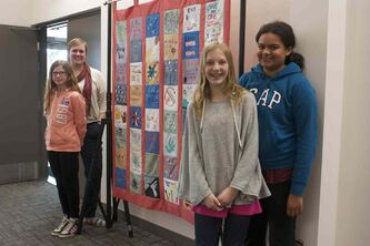 MBCI Grade 7 teacher Shawna McDowell and students Royan Reimer, Annalise Neufeld, and Khali McDowell are shown with their quilt project.